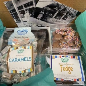 mailer showing Dolle's® postcards, bag of chocolate covered sea salt caramels, bag of non pareils, bag of plain caramels, and container of fudge