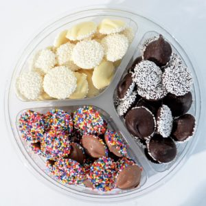 white, milk, and dark chocolate non pariels in a divided plastic container