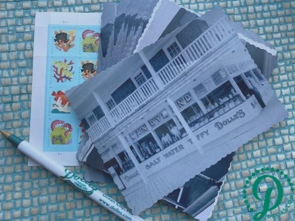stack of Dolle's® historic photo postcards with pen and stamps
