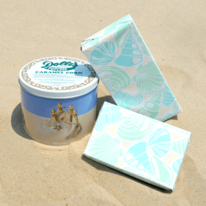 seashell decorated boxes of 1/2 lb homemade chocolates and 1 lb of Dolle's® salt water taffy, next to sand castle decorated 1/2 gal tin of caramel popcorn